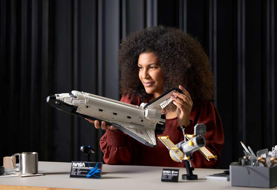 Imagen de estilo de vida de la mujer construyendo y viendo el descubrimiento del transbordador espacial LEGO de la NASA