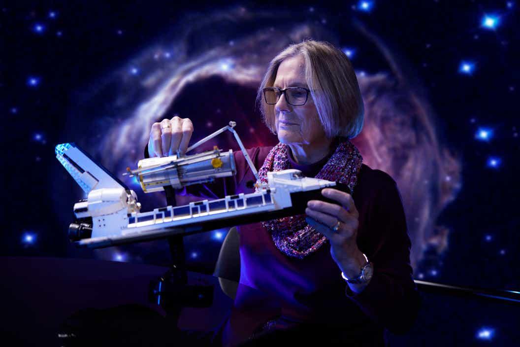 Imagen de la Dra. Kathy Sullivan sosteniendo el transbordador espacial LEGO Discovery de la NASA en su mano
